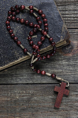 Rosary and old book on wooden table