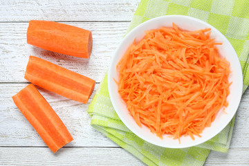 Raw grated carrots in bowl