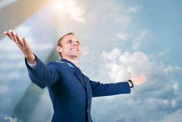 Happy young man aircraft pilot over blue sky  background