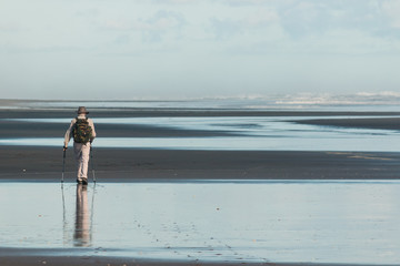 walker on Karekare beach, New Zealand