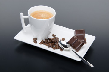 A cup of coffee with chocolate and coffee beans