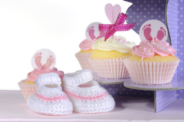 Baby girl cupcakes and booties, close up on cupcake stand