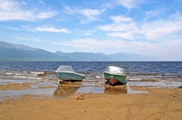 Two rusty motor boats at anchor on the beach at the shores of La