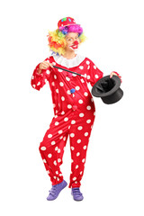 Female clown holding a magician hat