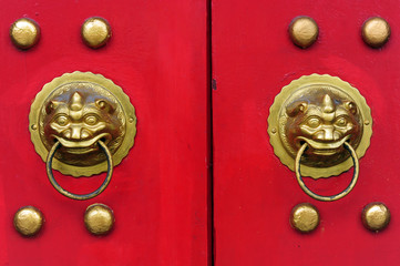 Red chinese door with a lion hand door