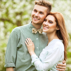 couple in love in park smiling holding a bouquet of lilac flower