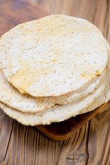 Mexican corn tortillas over wooden background, vertical shot