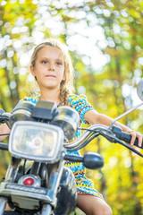 Little cheerful girl on old bike