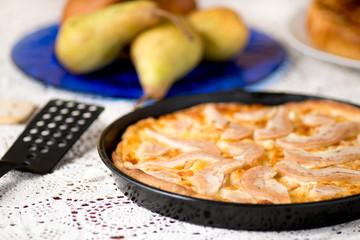 Pizza pere e brie nella teglia sul tavolo