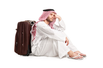 Sad Arabic man sitting on the floor