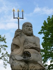 Poseidon statue with trident and fish against blue sky