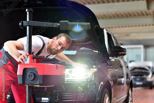 Lichttest // Automotive mechanic makes light test in workshop - 65026903