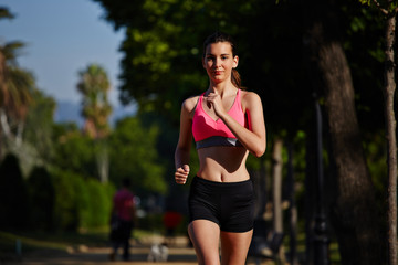 Beautiful girl in the sportwear running in the green park
