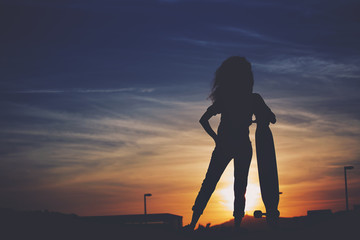 Silhouette of a slender girl with a longboard in sunset