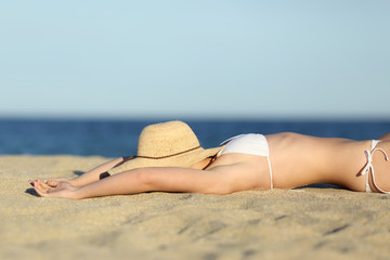 Woman resting sunbathing on the sand of the beach