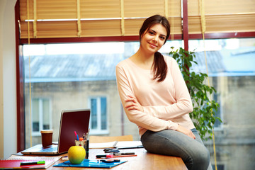 Young happy woman sitting on the table at her workplace