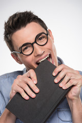attractive young man biting book.