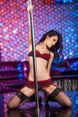 Beautiful brunet pole dancer in strip club.