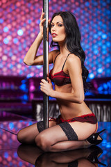 Sexy pole dancer looking at camera.