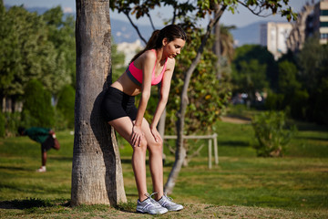 athletic girl leaned back against a tree tired after jogging