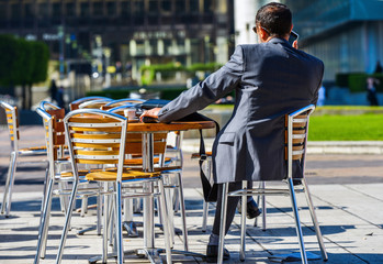 Modern businessman drinking a coffee while phoning