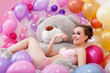 Smiling beautiful model posing with plush bear