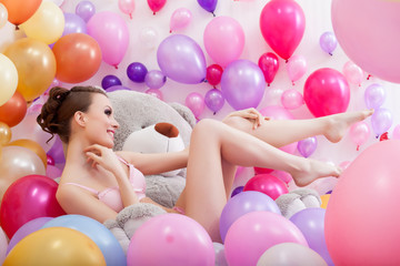 Pretty model posing with balloons and teddy bear