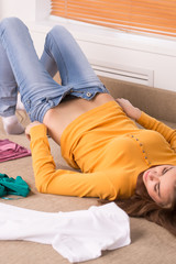 young woman dressing up jeans on sofa.