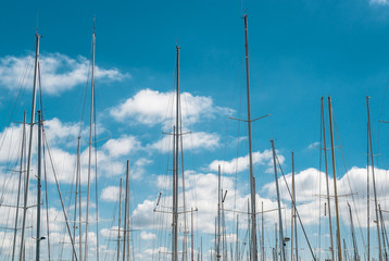 Ship masts over blue sky background