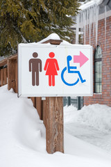 restroom sign in the snow