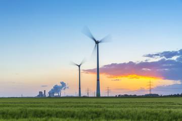 Windräder mit kohlekraftwerk im sonnenuntergang