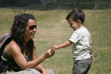 Niño dando flor a su madre en el campo