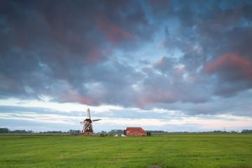 sunrise over windmill on Dutch farmland