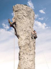 Climbers in action, young woman and man climbing difficult rock.