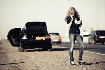 Young fashion woman with broken car calling for help