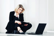Young business woman with laptop sitting at the wall