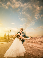 groom and bride dancing on a sunset vintage road