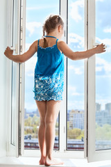 Young girl stands on opened window, looking from height