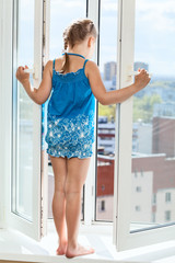 Girl teenager standing on window with opened door, looking down