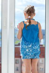 Rear view of girl in blue dress standing behind window glass
