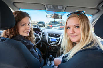 Two young pretty women sitting behind wheel of car, looking back