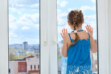 Little child looking through window glass, copyspace, rear view