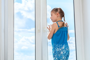Girl looking at blue sky through window, copyspace