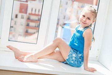 Jouful young girl in blue dress posing on window sill