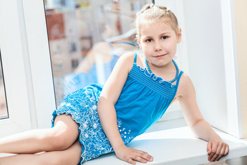 Calm pretty girl in blue dress laying on window sill