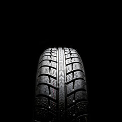 New car tyre on black background