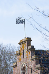 Windvane on hiostoric brick wall