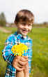 Child boy with dandelion on yellow meadow
