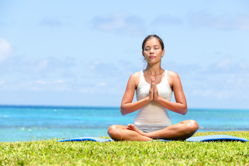 Meditation yoga woman on beach meditating by ocean