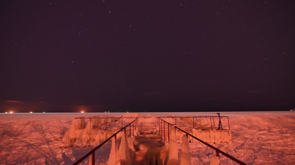Night frozen sea ise coast  pier - stars skyes timelapse